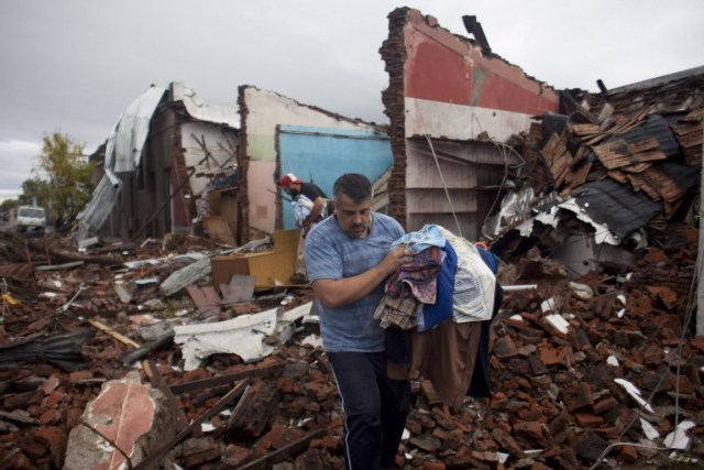 Residents salvage possessions from the remains of their house hit by a tornado in Dolores, Uruguay on April 16, 2016. At least four people were killed and seven severely injured Friday by a tornado 265 km west of Montevideo, official sources reported. / AFP PHOTO / Nicolas Garcia