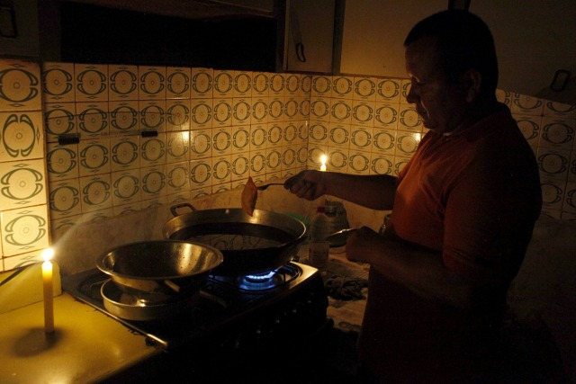 Un hombre cocina a la luz de las velas en San Cristóbal. Foto: REUTERS/Carlos Eduardo Ramirez