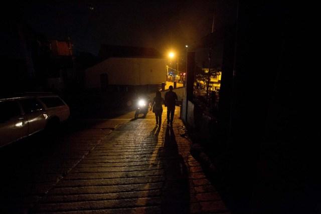 Residentes del municipio de El Hatillo,a las afueras de Caracas, se unen a pie a una protesta bloqueando las calles de los alrededores de su barrio que lleva 24 horas sin electricidad, el sábado 23 de abril de 2016. Los cortes de energía han agravado otros problemas de la vida cotidiana de los venezolanos. (Foto AP/Fernando Llano)