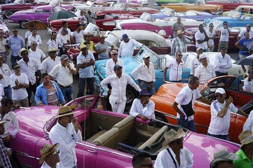 Conductores de autos estadounidenses clásicos reciben instrucciones finales sobre como traer a las modelos que participarían en el espectáculo de modas de Chanel, en el estacionamiento del Hotel Nacional, en La Habana, Cuba, el martes 3 de mayo de 2016. (Foto AP/Ramón Espinosa)