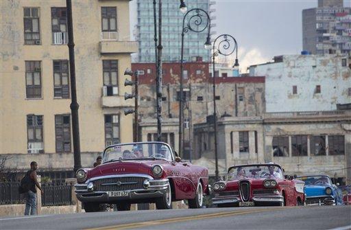 Varias modelos viajan en descapotables clásicos por el Malecón de La Habana para participar en el desfile de Chanel en La Habana, Cuba, el martes 3 de mayo de 2016. (AP Foto/Desmond Boylan)
