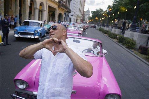 """El actor estadounidense Vin Diesel hace un gesto a la gente que ve la presentación de la colección """"cruise"""" del diseñador de moda Karl Lagerfeld para la casa Chanel, en el Paseo del Prado de La Habana, el martes 3 de mayo de 2016.  (AP Foto/Ramon Espinosa)"""