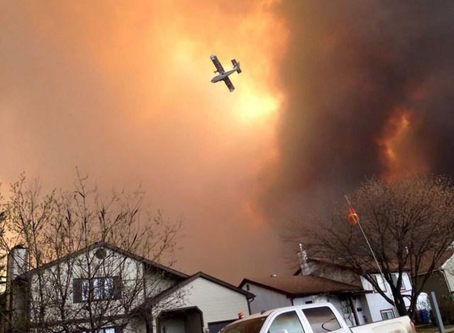 Humo cubre el aire y un pequeño avión sobrevuela Fort McMurray, Alberta, el martes 3 de mayo de 2016. La población completa de la ciudad canadiense en la región de arenas bituminosas Fort McMurray, Alberta, ha sido obligada a evacuar cuando las llamas de un incendio comenzaron a avanzar hacia ella. (Kitty Cochrane/The Canadian Press vía AP) CRÉDITO OBLIGATORIO