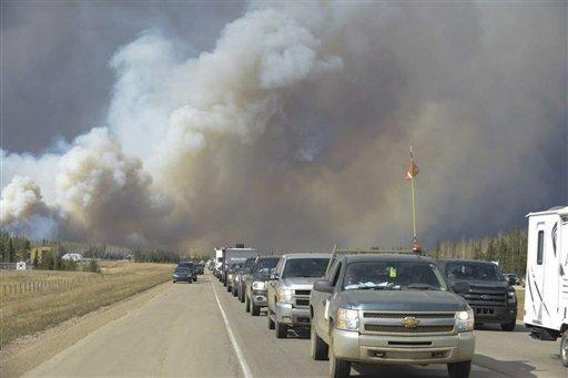Humo cubre el aire y árboles están en llamas en Fort McMurray, Alberta, el martes 3 de mayo de 2016. La población completa de la ciudad canadiense en la región de arenas bituminosas Fort McMurray, Alberta, ha sido obligada a evacuar cuando las llamas de un incendio comenzaron a avanzar hacia ella. (Kitty Cochrane/The Canadian Press vía AP) CRÉDITO OBLIGATORIO