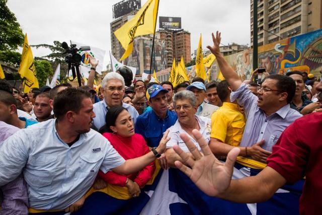 CAR03. CARACAS (VENEZUELA), 11/05/2016.- El líder opositor Henrique Capriles (c) y el presidente de la Asamblea Nacional de Venezuela, Henry Ramos Allup (c-d), participan en una manifestación hoy, miércoles 11 de mayo de 2016, en Caracas (Venezuela). La policía militarizada de Venezuela y la estatal Policía Nacional Bolivariana (PNB) impidieron el paso de la marcha a la que convocó hoy la oposición del país hasta la sede del Poder Electoral para pedir celeridad en la activación de un referendo para revocar al presidente, Nicolás Maduro. EFE/Miguel Gutiérrez