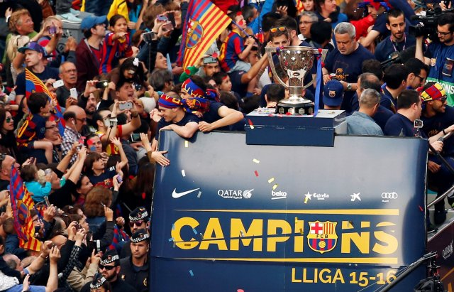 Barcelona's players and staff members on an open-top bus celebrate with their supporters during a parade along the streets of Barcelona, after winning the Spanish Liga, in Barcelona, Spain, May 15, 2016. REUTERS/Albert Gea TPX IMAGES OF THE DAY