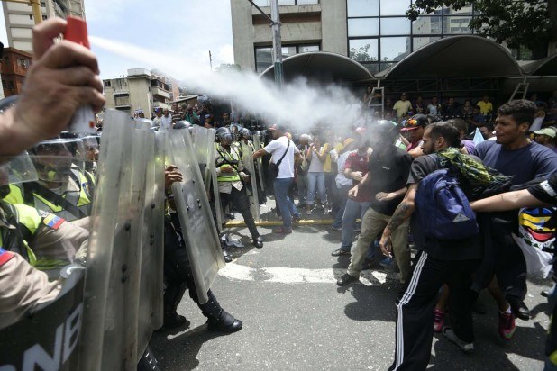 People clash with police as they protest against new emergency powers decreed this week by President Nicolas Maduro in Caracas on May 18, 2016.  Public outrage was expected to spill onto the streets of Venezuela Wednesday, with planned nationwide protests marking a new low point in Maduro's unpopular rule. / AFP PHOTO / JUAN BARRETO