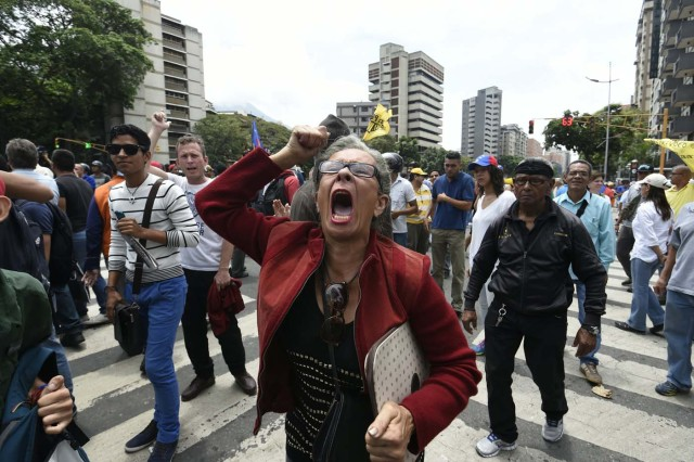 Demonstrators protest against new emergency powers decreed this week by President Nicolas Maduro in Caracas on May 18, 2016.  Public outrage was expected to spill onto the streets of Venezuela Wednesday, with planned nationwide protests marking a new low point in Maduro's unpopular rule. / AFP PHOTO / JUAN BARRETO