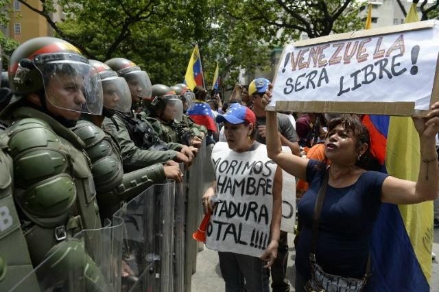 """La gente protesta con carteles que decían """"Venezuela será libre"""" y """"Nos morimos de hambre. Dictadura total"""" contra los nuevos poderes de emergencia decretado esta semana por el presidente Nicolás Maduro, frente a una línea de policías en Caracas el 18 de mayo de 2016. Se esperaba ultraje público a derramarse sobre las calles de Venezuela miércoles, con protestas a nivel nacional previstas marca un nuevo punto bajo en regla impopular de Maduro. FEDERICO PARRA / AFP"""