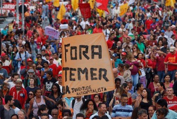 """Con un letrero que dice """"Fuera Temer"""", manifestantes marchan en contra del presidente interino de Brasil, Michel Temer, y en apoyo a la suspendida mandataria, Dilma Rousseff, el domingo 22 de mayo de 2016 en Río de Janeiro, Brasil. (Foto AP/Andre Penner)"""