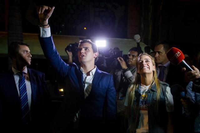 El líder del partido español Ciudadanos, Albert Rivera, y Lilian Tintori, esposa de   Leopoldo López, saludan al opositor encarcelado Daniel Ceballos a las afueras de su residencia en la ciudad de Caracas (Venezuela).  EFE