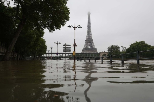 A picture taken on June 2, 2016 shows the river Seine bursting its banks next to the Eiffel Tower in Paris. Officials were putting up emergency flood barriers on June 2 along the swollen river Seine after days of torrential rain -- including near the Louvre, home to priceless works of art. AFP PHOTO / KENZO TRIBOUILLARD / AFP PHOTO / KENZO TRIBOUILLARD