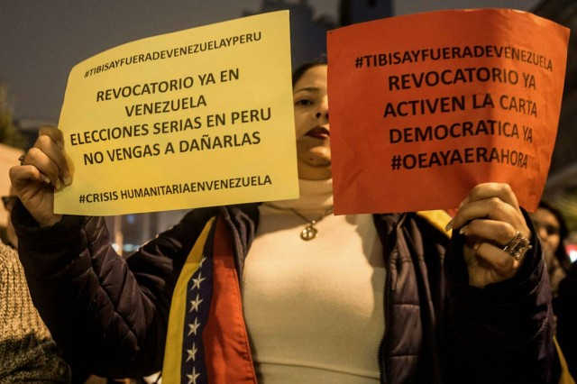 Venezuelan citizens in Peru hold signs during a protest against the visit of the president of the Venezuelan National Electoral Board (TSJ), Tibisay Lucena (not in frame), in Lima on June 01, 2016.  / AFP PHOTO / ERNESTO BENAVIDES