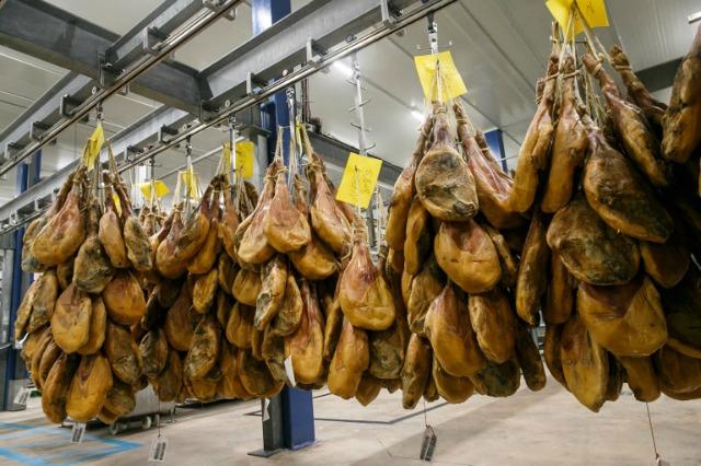 Una imagen tomada el 2 de junio el año 2016 muestra el jamón que cuelga en una línea de producción de la fábrica de Navidul en Burgos. CESAR MANSO / AFP