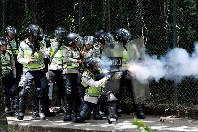 A riot police fires tear gas towards demonstrators during a protest called by university students against Venezuela's government in Caracas