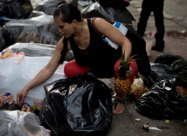 En esta foto del 2 de junio de 2016, una mujer embarazada que pidió no ser identificada recoge fruta en el basural del mercado Coche en Caracas, Venezuela. Productos básicos como la harina y el aceite de cocina están subsidiados y cuestan centavos, pero frutas y verduras se han convertido en un lujo fuera del alcance de muchas familias venezolanas. (AP Foto/Fernando Llano)