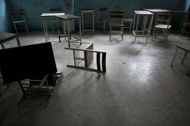 Fotografía del 1 de junio de 2016 muestra sillas y escritorios en un salón de clases abandonado en una escuela secundaria pública en Caracas, Venezuela. Oficialmente, Venezuela canceló este año 16 días de escuela, incluyendo clases del viernes, debido a una crisis de producción de electricidad. En realidad, los niños venezolanos están perdiendo ahora un promedio de 40% de tiempo de clases, calculó un grupo de padres de familia, y una tercera parte de los maestros falta a clases cualquier día dado para formarse en filas para conseguir alimento. (AP Foto/Ariana Cubillos)
