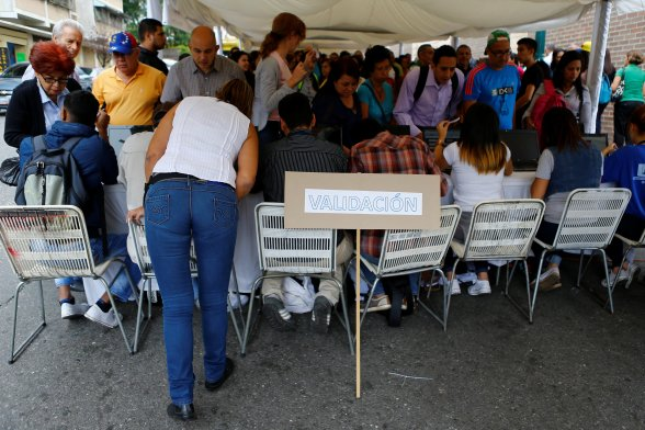 "People stand in line as they gather outside a validation center during Venezuela's National Electoral Council (CNE) second phase of verifying signatures for a recall referendum against President Nicolas Maduro in Caracas, Venezuela, June 20, 2016. The placard reads ""Validation"". REUTERS/Ivan Alvarado"