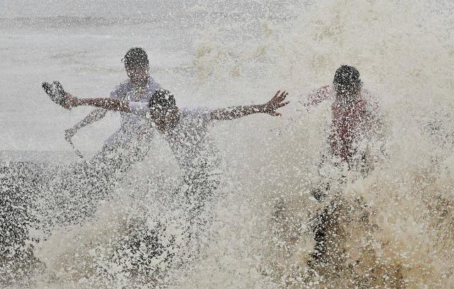 Los hombres se empapan por una gran ola durante la marea alta en la primera línea de mar en Mumbai, India, 23 de junio de 2016. REUTERS / Shailesh Andrade