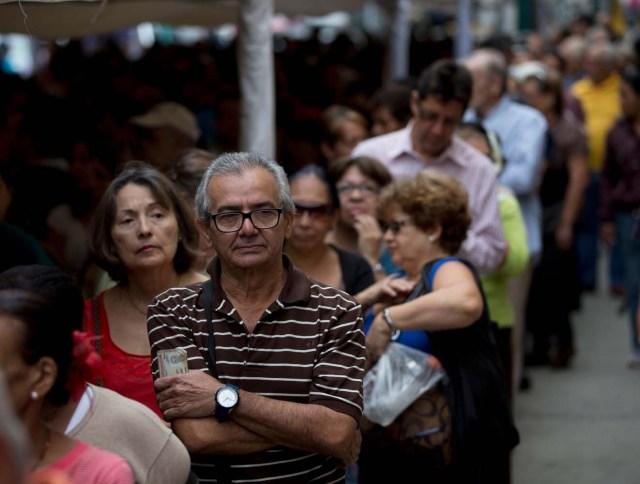 La gente hace fila para certificar sus firmas en la sede del Consejo Nacional Electoral de Venezuela, CNE, en Caracas, Venezuela, el lunes 20 de junio de 2016. Para activar una nueva etapa del proceso del referendo revocatorio del mandato del presidente Nicolás Maduro, la oposición debe lograr la validación de al menos 196.000 firmas. De superarse esta etapa la oposición deberá emprender la recolección de más de cuatro millones de firmas para lograr activar formalmente la consulta popular. (Foto AP / Fernando Llano)