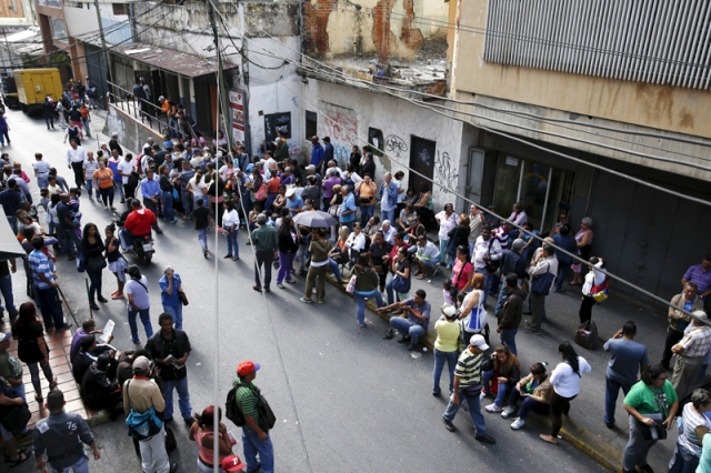 People queue to try to buy basic food items outside a supermarket in Caracas
