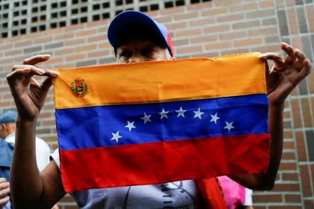 Una mujer sostiene una bandera de Venezuela a las afueras de un centro de validación durante la segunda fase de verificación de firmas para solicitar un referéndum contra el presidente Nicolás Maduro, Caracas, Venezuela, 20 de junio del 2016. Un grupo de venezolanos pedirá en septiembre a Estados Unidos que revise los expedientes migratorios de 89 compatriotas que viven en ese país y que habrían hecho fortunas producto de sus vínculos con los gobiernos socialistas de Hugo Chávez y Nicolás Maduro, dijo un ex juez que lidera la iniciativa. REUTERS/Ivan Alvarado