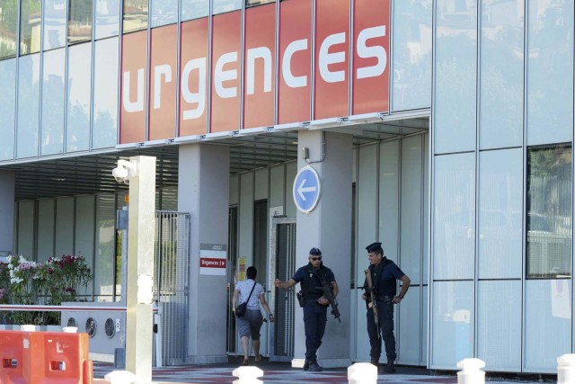 Armed French police secure the entrance to the Pasteur Hospital the day after a truck ran into a crowd at high speed killing scores and injuring more who were celebrating the Bastille Day national holiday in Nice, France, July 15, 2016. REUTERS/Jean-Pierre Amet