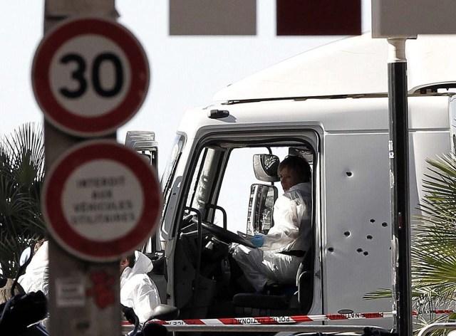 """GRA013. NIZA, 15/07/2016.- Investigadores de la policia en la cabina del camión que anoche arrolló a una multitud que presenciaba los fuegos artificiales de la fiesta nacional del 14 de Julio en Niza, causando la muerte de al menos 90 personas. La Fiscalía Antiterrorista ha asumido la investigación del caso. El propio presidente del país, François Hollande, dijo en un mensaje a la nación que """"no se puede negar el carácter terrorista"""" del acto, y añadió que """"toda Francia está bajo la amenaza del terrorismo islamista"""". El conductor del camión, único ocupante del vehículo, fue abatido por las fuerzas de seguridad tras haber recorrido unos dos kilómetros por el Paseo de los Ingleses, uno de los más emblemáticos de la ciudad mediterránea, embistiendo a su paso a todo aquel con quien se cruzaba. EFE/Alberto Estévez"""