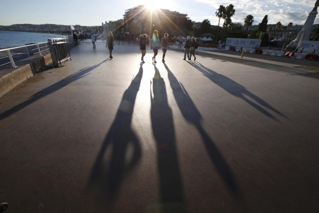 The sun casts long shadows as people walk on the Promenade des Anglais the day after a truckran into a crowd at high speed killing scores and injuring more who were celebrating the Bastille Day national holiday, in Nice, France, July 15, 2016. REUTERS/Eric Gaillard