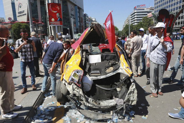 People look at a destroyed car as they march from Kizilay square towards the Turkish General Staff building in Ankara, on July 16, 2016, following a failed coup attempt. Turkish authorities said they had regained control of the country on July 16 after thwarting a coup attempt by discontented soldiers to seize power from President Recep Tayyip Erdogan that claimed more than 250 lives. / AFP PHOTO / ADEM ALTAN