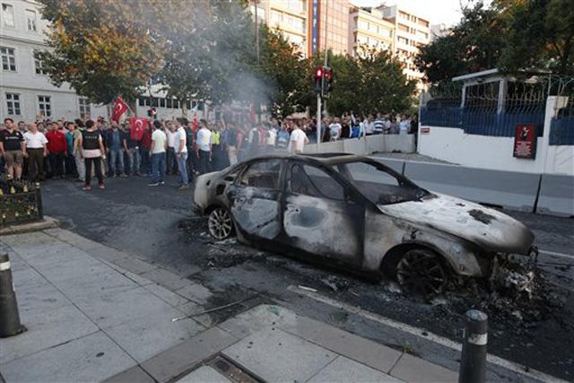 TUrcos reunidos ante un auto quemado en Estambul, el sábado 16 de julio de 2016. El presidente de Turquía, Recep Tayyip Erdogan, declaró el sábado de madrugada que tenía el control del país tras un intento de golpe de Estado. (AP Foto/Emrah Gurel)