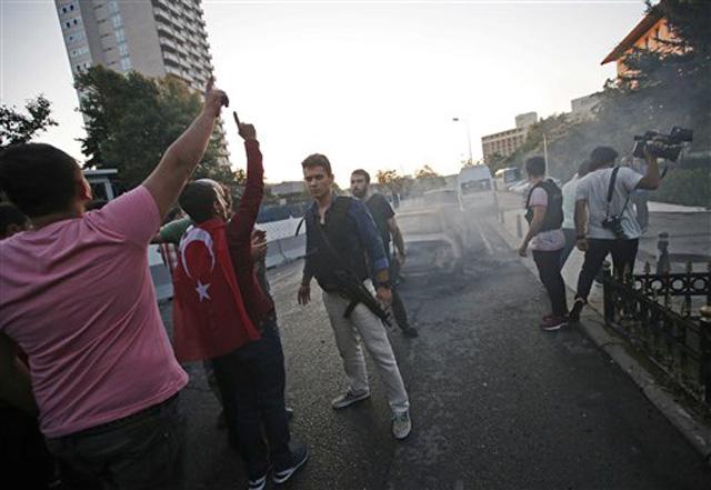 Turcos celebrando mientras agentes de policía leales al gobierno aseguran una zona de Estambul, el sábado 16 de julio de 2016. El presidente de Turquía, Recep Tayyip Erdogan, declaró el sábado de madrugada que tenía el control del país tras un intento de golpe de Estado. (AP Foto/Emrah Gurel)