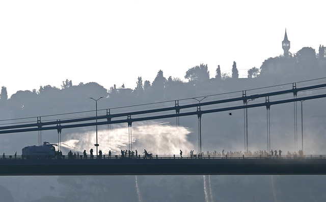 A police armored vehicle uses a water cannon to disperse anti-goverment forces on Bosphorus Bridge in Istanbul, Turkey, July 16, 2016. REUTERS/Murad Sezer