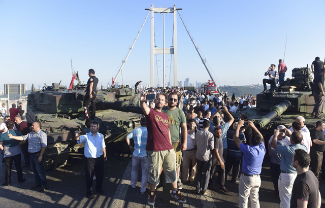 People take selfies after soldiers involved in the coup surrendered on the Bosphorus Bridge in Istanbul, Turkey July 16, 2016. REUTERS/Yagiz Karahan TPX IMAGES OF THE DAY
