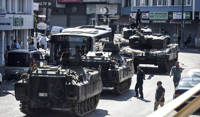 """This picture taken on July 16, 2016 shows abandonned tanks in the street after police took over the military position at the Anatolian side at Uskudar in Istanbul. President Recep Tayyip Erdogan urged Turks to remain on the streets on July 16, 2016, as his forces regained control after a spectacular coup bid by discontented soldiers that claimed more than 250 lives. Describing the attempted coup as a """"black stain"""" on Turkey's democracy, Yildirim said that 161 people had been killed in the night of violence and 1,440 wounded. / AFP PHOTO / BULENT KILIC"""