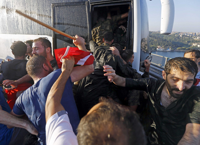 Soldiers push each other to board a bus to escape the mob after troops involved in the coup surrendered on the Bosphorus Bridge in Istanbul, Turkey July 16, 2016. REUTERS/Murad Sezer