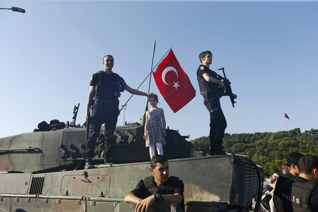 Policemen stand on a military vehicle after troops involved in the coup surrendered on the Bosphorus Bridge in Istanbul, Turkey July 16, 2016. REUTERS/Murad Sezer