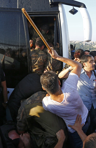 Soldiers are beaten by the mob as they board a bus after troops involved in the coup surrendered on the Bosphorus Bridge in Istanbul, Turkey July 16, 2016. REUTERS/Murad Sezer