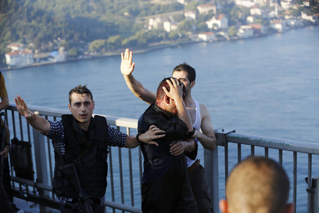 Policemen protect a soldier from the mob after troops involved in the coup surrendered on the Bosphorus Bridge in Istanbul, Turkey July 16, 2016. REUTERS/Murad Sezer