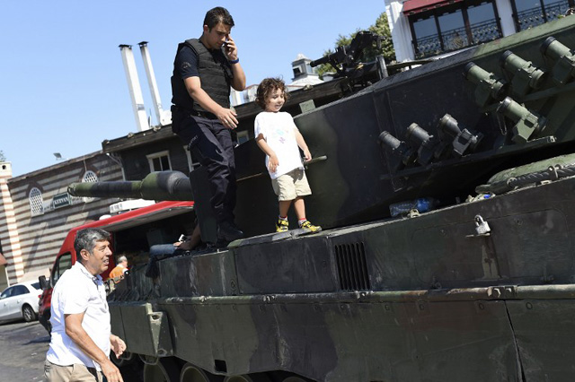 """EDITORS NOTE: Graphic content / A child walks next to a police officer on a tank after the military position was taken over at the Anatolian side at Uskudar in Istanbul on July 16, 2016, following an attempt by discontented soldiers to seize power from President Recep Tayyip Erdogan that claimed more than 250 lives. After the bloodiest challenge to his 13-year autocratic rule, Erdogan urged his backers to stay on the streets to prevent a possible """"flare-up"""" of yesterday's chaos in the strategic NATO member of 80 million people. / AFP PHOTO / BULENT KILIC"""