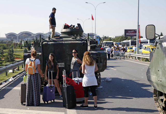 Women stand behind a military vehicle in front of Sabiha Airport, in Istanbul, Turkey July 16, 2016. REUTERS/Baz Ratner