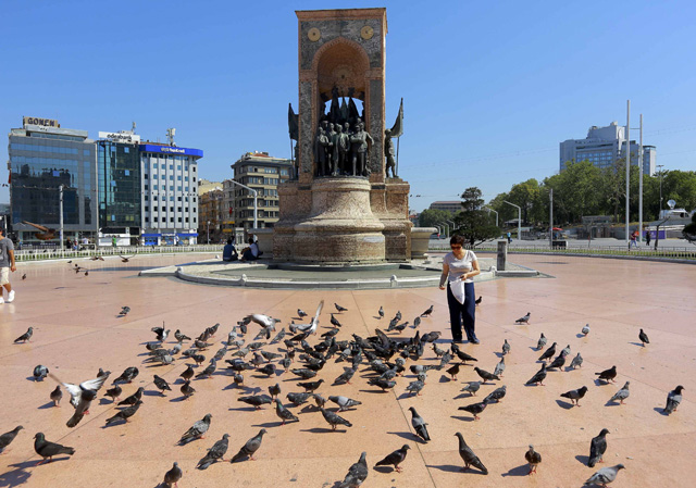 A woman feeds pigeons in front of the Republic Monument at Taksim Square in Istanbul after an attempted coup in Turkey, July 16, 2016. REUTERS/Kemal Aslan