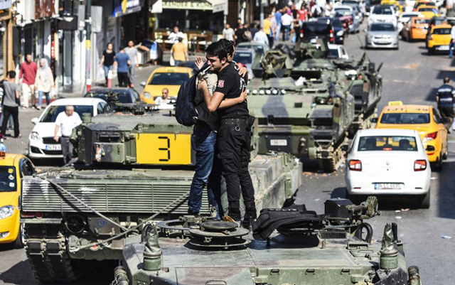 """Turkish police officer (R) embrace a man on a tank after the military position was taken over at the Anatolian side at Uskudar in Istanbul on July 16, 2016. President Recep Tayyip Erdogan urged Turks to remain on the streets on July 16, 2016, as his forces regained control after a spectacular coup bid by discontented soldiers that claimed more than 250 lives. Describing the attempted coup as a """"black stain"""" on Turkey's democracy, Yildirim said that 161 people had been killed in the night of violence and 1,440 wounded. / AFP PHOTO / BULENT KILIC"""