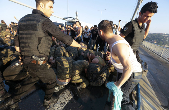 A police officer protects urrendered Turkish soldiers who were involved in the coup on Bosphorus bridge in Istanbul, Turkey, July 16, 2016. REUTERS/Stringer EDITORIAL USE ONLY. NO RESALES. NO ARCHIVES.