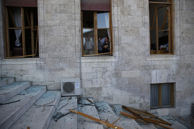 People look through broken windows of the parliament building in Ankara, Turkey, July 16, 2016. REUTERS/Baz Ratner