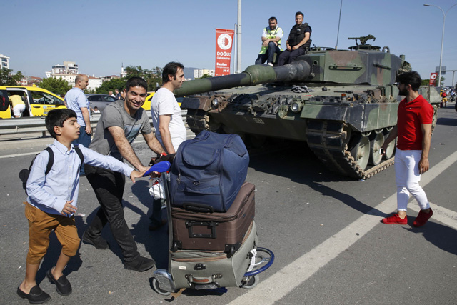 REFILE - CORRECTING CITY - People walk past Turkish police officers sitting on a Leopard 2 tank in Istanbul, Turkey, July 16, 2016. REUTERS/Baz Ratner
