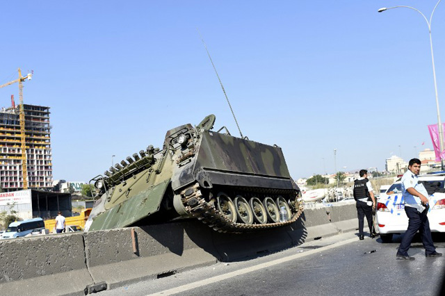 """This picture taken on July 16, 2016 shows a tank stucks on a median strip as Turkish police officers walk around it after they took over a military position at the Anatolian side at Uskudar in Istanbul on July 16, 2016. President Recep Tayyip Erdogan urged Turks to remain on the streets on July 16, 2016, as his forces regained control after a spectacular coup bid by discontented soldiers that claimed more than 250 lives. Describing the attempted coup as a """"black stain"""" on Turkey's democracy, Yildirim said that 161 people had been killed in the night of violence and 1,440 wounded. / AFP PHOTO / BULENT KILIC"""