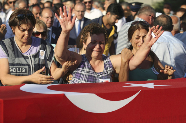 Women mourn over the coffin holding body of police officer Nedip Cengiz Eker during a funeral ceremony in Marmaris, Turkey, July 16, 2016. REUTERS/Kenan Gurbuz