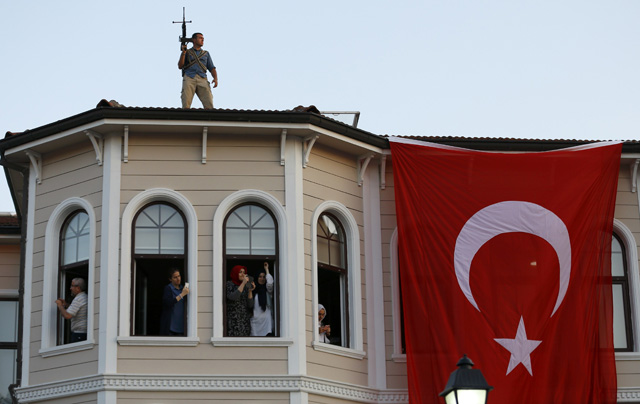 People try to take pictures of Turkish President Tayyip Erdogan walking through the crowd of supporters, as a security officer stands on the roof in Istanbul, Turkey, July 16, 2016. REUTERS/Murad Sezer