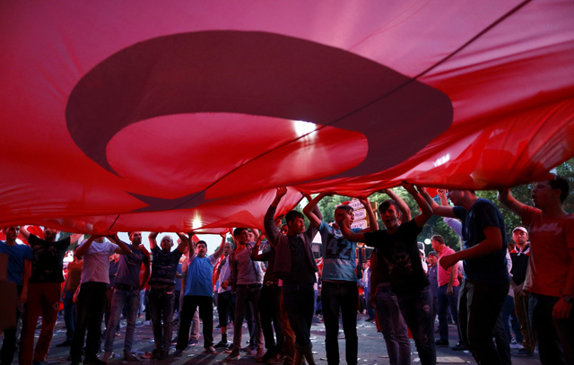 Supporters of Turkish President Tayyip Erdogan hold a giant Turkish flag during a demonstration outside parliament building in Ankara, Turkey, July 16, 2016. REUTERS/Osman Orsal TPX IMAGES OF THE DAY